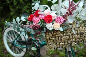 bela bicicleta com flores em uma cesta fica em uma avenida foto
