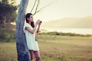 Uma linda fotógrafa segurando uma câmera retro foto