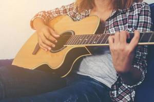 mulher jovem hippie tocando violão foto