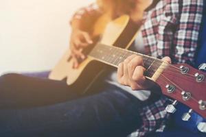 mulher jovem hippie tocando uma guitarra. foto