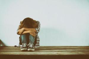 mulher triste abraça o joelho dela ninguém foto