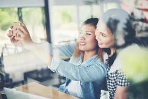 dois amigos desfrutando de uma selfie junto com o reflexo da janela foto