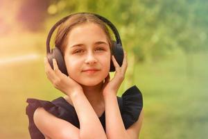 colegial no parque ouve música com fones de ouvido. foto