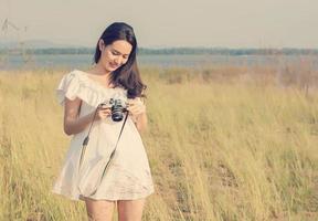 Mulher fotógrafa segurando uma câmera retro com o nascer do sol foto