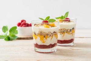 manga fresca caseira e framboesa fresca com iogurte e granola - estilo de comida saudável foto
