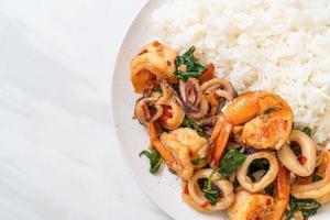 arroz e frutos do mar fritos de camarão e lula com manjericão tailandês - comida asiática foto