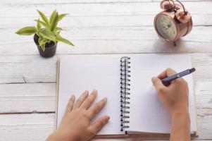 mão escrevendo com livros e relógio na mesa foto