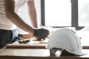 foco no capacete de segurança na mesa de trabalho e carpinteiro foto