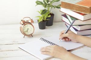 mão escrevendo papel na mesa e local de trabalho com relógio, livro e palnt foto