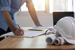 engenheiro ou arquiteto desenhando e escrevendo em uma folha de papel na mesa foto
