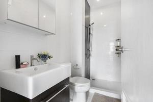 banheiro moderno e branco de madeira com box de vidro no apartamento foto