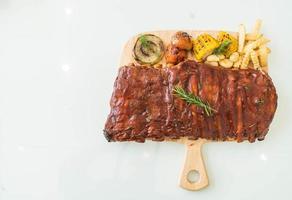 Costela de porco grelhada com molho barbecue e vegetais e batatas fritas foto