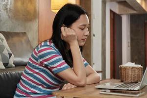mulher asiática trabalhando em casa, cochilando e cochilando atrás de um laptop. foto