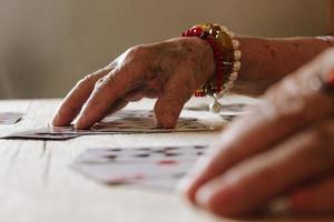 leitura de cartas de adivinhação, magia da avó, leitura da sorte, mãos de mulheres foto