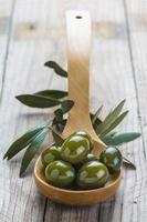 colher de pau com azeitonas e azeite foto