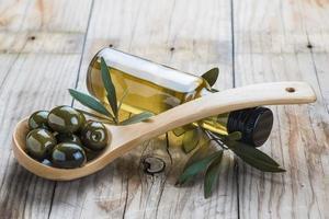 garrafa de azeite e uma colher com azeitonas foto