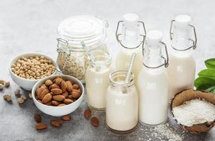 tipos alternativos de leites veganos em garrafas de vidro foto