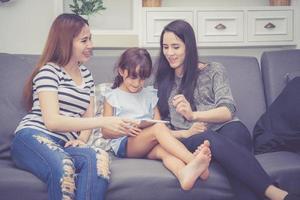 mãe, tia e filho se divertindo juntos, aprendendo com o uso do tablet foto
