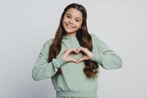 atraente e fofa adolescente mostrando um gesto vindo do coração foto