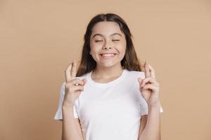 adolescente engraçada e fofa cruzou os dedos e fechou os olhos foto