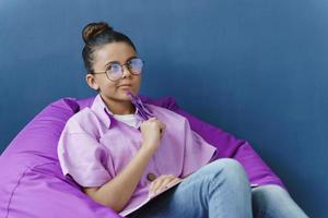 garota focada de óculos está pensando em algo muito importante foto