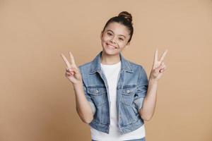 adolescente sorridente e positiva mostrando um gesto em v foto