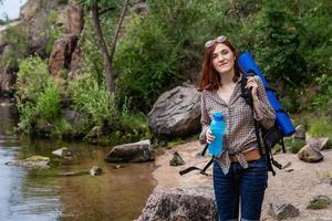 turista mulher com uma mochila, um fundo de montanhas e rios foto