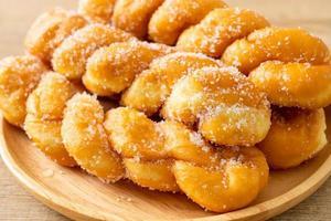 donut de açúcar em forma de espiral na placa de madeira foto