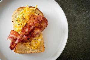 torrada de pão com ovo mexido e bacon em prato branco foto