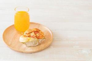 Pão de maionese de linguiça com suco de laranja no prato de madeira foto