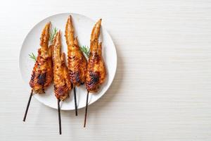 espeto de asas de frango grelhado ou churrasco no prato foto