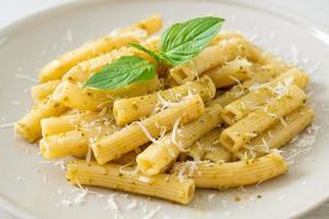 macarrão pesto rigatoni com queijo parmesão - comida italiana e comida vegetariana foto
