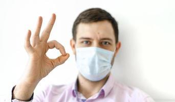 um homem com uma camisa e uma máscara protetora. mostra sinal de bom. foto