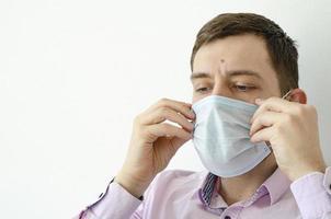 um homem com uma camisa coloca uma máscara. proteção contra o vírus. foto