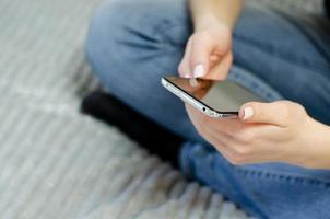 uma jovem está usando o telefone celular. comunicação à distância. foto