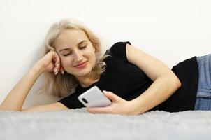 a menina lê a boa notícia ao telefone. redes sociais. foto