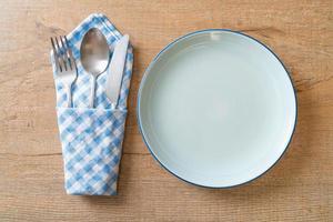 prato vazio ou prato com faca, garfo e colher no fundo de ladrilhos de madeira foto