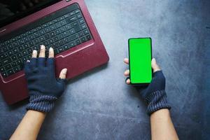Mão de hacker roubando dados de telefone inteligente foto