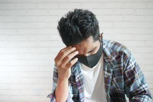 jovem doente com máscara facial sofrendo de dor de cabeça foto