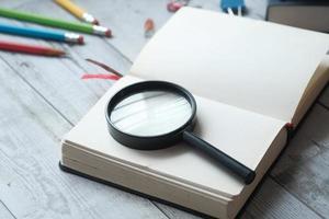 livro aberto e lupa na mesa. foto