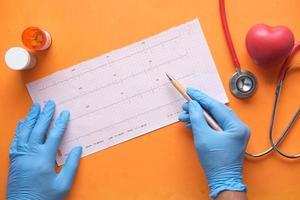médico mão em luvas médicas, analisando o diagrama cardiovascular. foto
