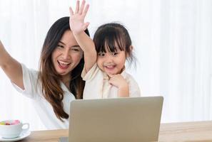 mãe asiática jogando jogo de computador com criança na sala de estar foto