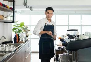 barista asiático usando uma máquina de moer café para moer grãos de café foto