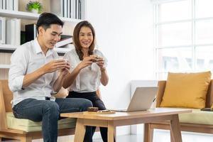 mulher asiática e homem sentados no café tomando café expresso foto