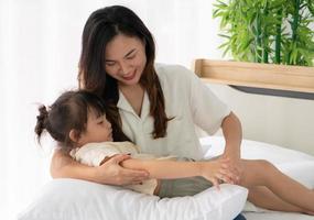 mãe asiática abraçando criança no quarto foto