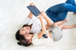 mãe asiática assistindo desenho animado em tablet com criança pequena em casa foto