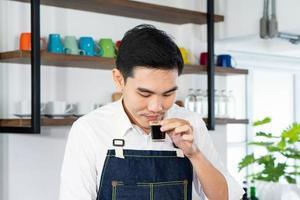 jovem barista asiática aprecia o cheiro de café quente no café foto