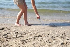 jovem pegar uma garrafa de plástico usada da praia para limpar a costa foto