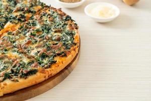 Pizza de espinafre e queijo em bandeja de madeira - estilo de comida vegana e vegetariana foto