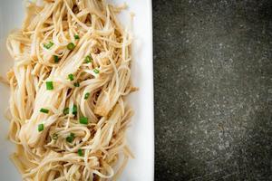 Cogumelo agulha dourado frito com manteiga no prato branco foto